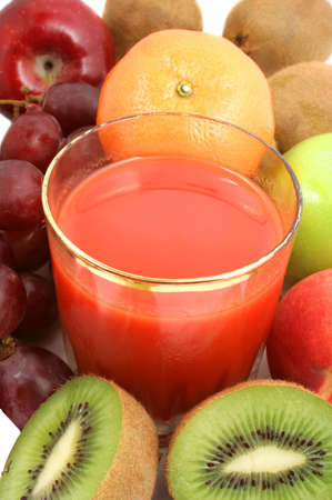 Variety of fresh organic fruits and  red tomato juice in a clear glass Stock Photo