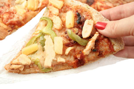 picking up a slice of multigrain crust pizza with different types of toppings like chicken, green peppers, and pineapple photo