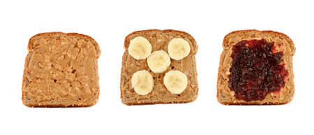 Three pieces of toasted bread with crunchy peanut butter on whole wheat toast topped with banana slices or raspberry jam, isolated on a white background photo