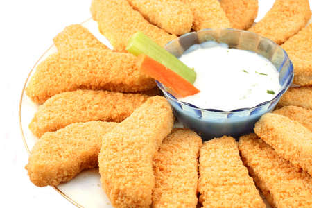 A plate of crispy chicken fingers with  vegetables and dip on a white background Stock Photo