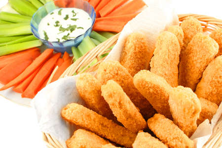 A basket of crispy chicken fingers with platter of vegetables and dip on a white background Stock Photo