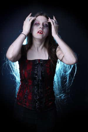 De vampier van de vrouw met lang haar, tanden, claws en dripping bloed van lippen.
