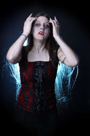 Woman vampire with long hair, fangs, claws and dripping blood from lips.