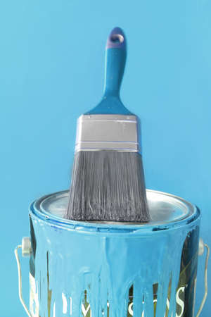 Paintbrush on top of light blue  paint can for diy home decorating