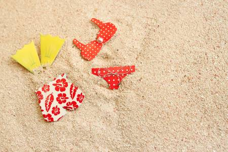 Men's and women's bathing suits in beach sand, great for a summer background