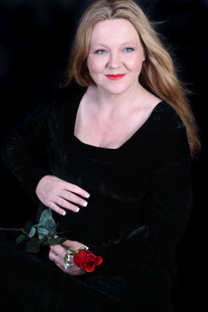 velvet dress: Pretty Irish woman with blonde hair touching her pregnant belly dressed in a black velvet dress holding a  red rose