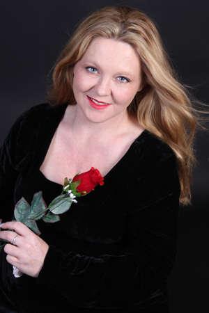 velvet dress: Pretty blonde woman of Irish descent in her thirties wearing a black velvet dress holding a red rose