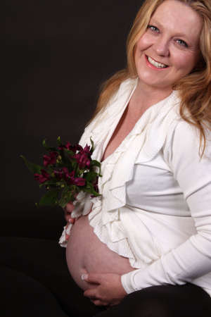 Pretty Irish woman with blonde hair in her third trimester sitting and touching her pregnant belly on a black background photo