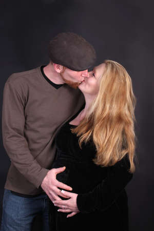 Loving kissing  couple expecting baby, both are touching womans pregnant belly on a black background photo