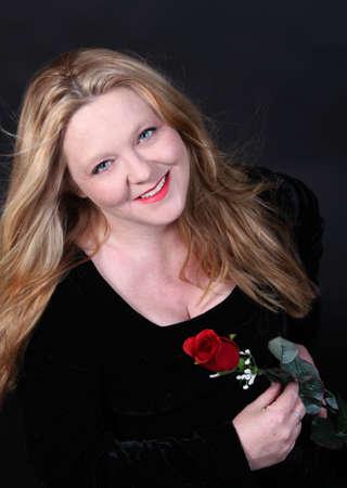 velvet dress: Pretty Irish woman with blonde hair  belly dressed in a black velvet dress holding a  red rose