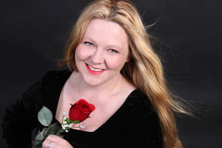 velvet dress: Pretty Irish woman with blonde hair  dressed in a black velvet dress holding a  red rose