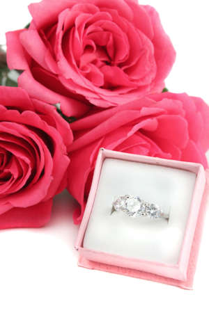 Sparkling diamond engagement ring in box with three pink roses in background great for valentines photo
