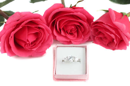 Sparkling diamond engagement ring in box with three pink roses in background great for valentines (not isolated) Imagens