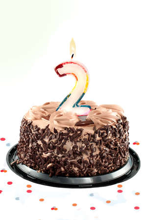 Chocolate birthday cake surrounded by confetti with lit candle for a second birthday or anniversary celebration Stock Photo