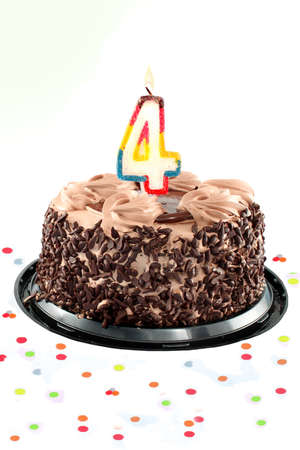 Chocolate birthday cake surrounded by confetti with lit candle for a fourth birthday or anniversary celebration photo