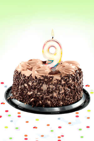 Chocolate birthday cake surrounded by confetti with lit candle for a ninth birthday or anniversary celebration photo
