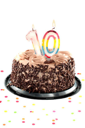 10 years: Chocolate birthday cake surrounded by confetti with lit candle for a tenth birthday or anniversary celebration Stock Photo