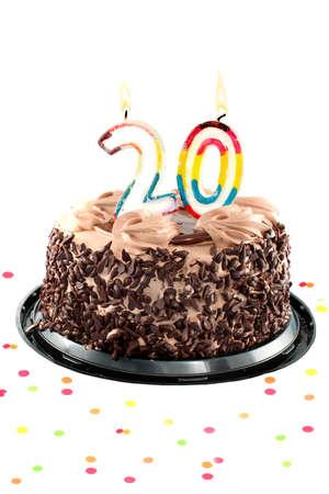 20: Pastel de chocolate de cumplea�os rodeado de confeti con una vela encendida para una celebraci�n de cumplea�os o aniversario XX  Foto de archivo
