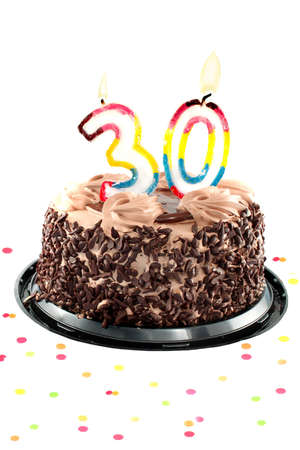 Chocolate birthday cake surrounded by confetti with lit candle for a thirtieth birthday or anniversary celebration