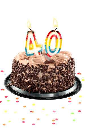 Chocolate birthday cake surrounded by confetti with lit candle for a fortieth birthday or anniversary celebration