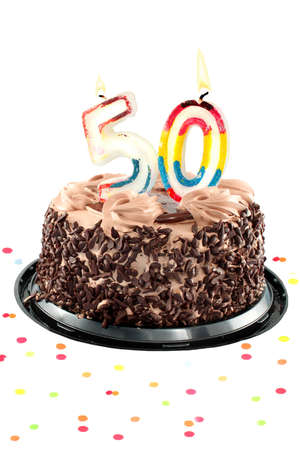 Chocolate birthday cake surrounded by confetti with lit candle for a fiftieth birthday or anniversary celebration