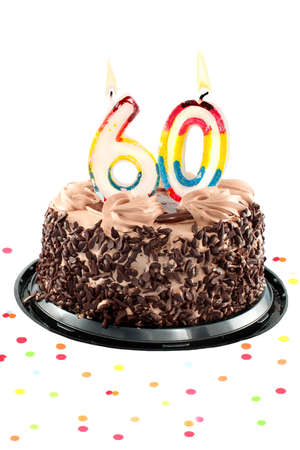 Chocolate birthday cake surrounded by confetti with lit candle for a sixtieth birthday or anniversary celebration