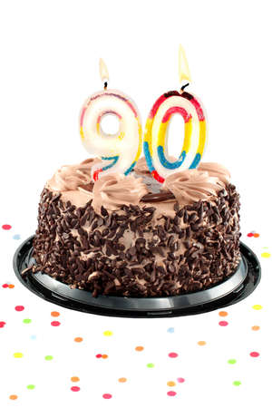 Chocolate birthday cake surrounded by confetti with lit candle for a ninetieth birthday or anniversary celebration