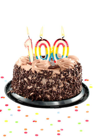 Chocolate birthday cake surrounded by confetti with lit candles for a century, one hudredth birthday or anniversary celebration Stock Photo