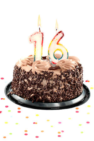 number 16: Chocolate birthday cake surrounded by confetti with lit candle for an sixteenth  birthday or anniversary celebration Stock Photo