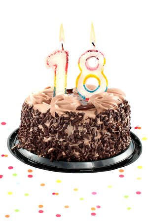 Chocolate birthday cake surrounded by confetti with lit candle for an eighteenth  birthday or anniversary celebration Imagens