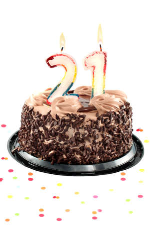 Chocolate birthday cake surrounded by confetti with lit candle for a twenty first  birthday or anniversary celebration photo