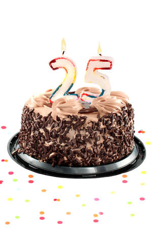 Chocolate birthday cake surrounded by confetti with lit candle for a twenty fifth birthday or anniversary celebration