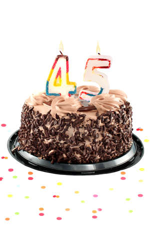 Chocolate birthday cake surrounded by confetti with lit candle for a forty fifth birthday or anniversary celebration