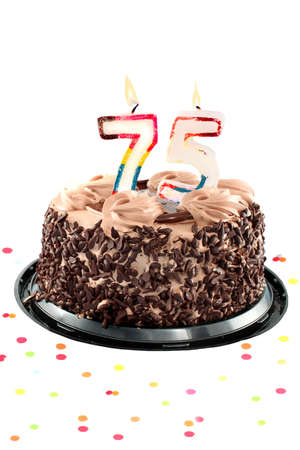 Chocolate birthday cake surrounded by confetti with lit candle for a seventy fifth birthday or anniversary celebration photo