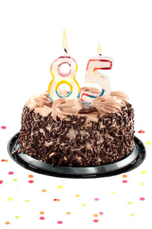 Chocolate birthday cake surrounded by confetti with lit candle for a eighty fifth birthday or anniversary celebration