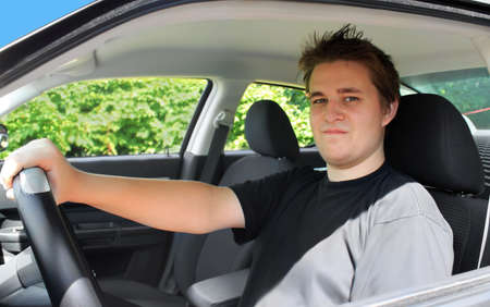 Newly lisenced male teen sitting behind the wheel and ready to drive a modern car