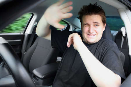Young male driver raises his arms afraid for his life while accident happens while not wearing a seatbelt in car Archivio Fotografico
