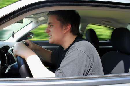 Angry young male driver speeding very fast showing anger as roadrage Stock Photo - 7528409