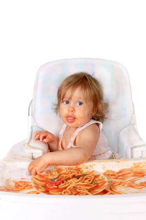 Young blue eyed baby girl making a mess with spaghetti in tomato sauce on a white background Archivio Fotografico