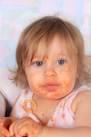 Young blue eyed baby girl making a mess on her face with spaghetti and tomato sauce with pieces in her shirt photo