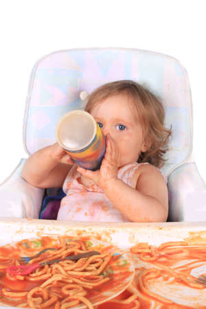 Young blue eyed baby girl making a mess with spaghetti in tomato sauce and having juice from cup on a white background