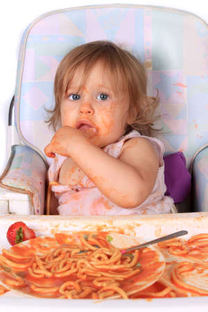 mess: Young blue eyed baby girl making a mess with spaghetti in tomato sauce on a white background Stock Photo
