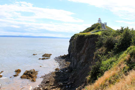enrage: Lighthouse on cliff of Cape Enrage, part of the dramatic landscape  in New Brunswick, Canada