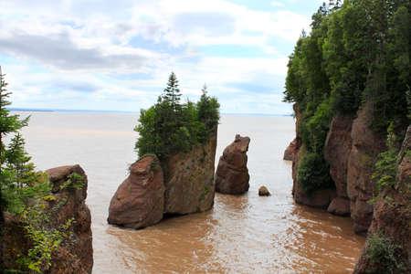turismo ecologico: Fangosas aguas con la marea alta, con vistas a las rocas de maceta en Hopewell Rocks, Nuevo Brunswick, Canad�