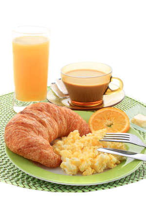 Continental hotel breakfast with scrambled eggs, croissant, coffe, and orange juice  photo