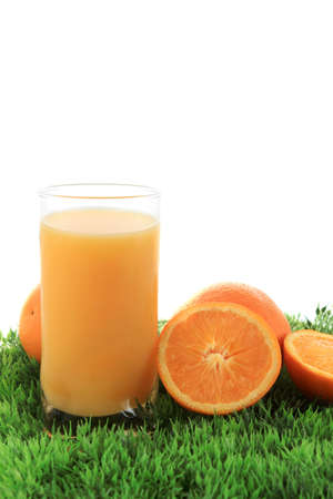 cut grass: Orange juice and cut fruit on green grass isolated on a white background