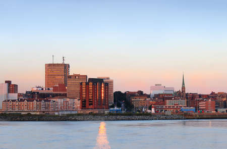 maritimes: City view of dowtown area of Saint John, New Brunswick, Canada at sunset with sun reflections in the water from buidling
