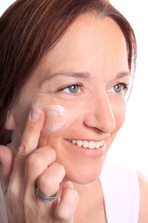 Pretty woman in her early forties with green eyes and beautiful smile applying moisturizing facial cream on her cheek