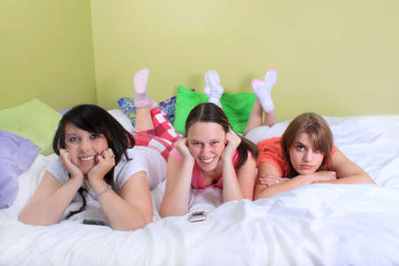 slumber: Group of three teenage girls hanging out on a bed in their pyjamas ready for a sleepover or slumber party