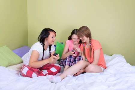 Three pretty teenage girls react surprised or shocked by reading a text message from a mobile phone photo